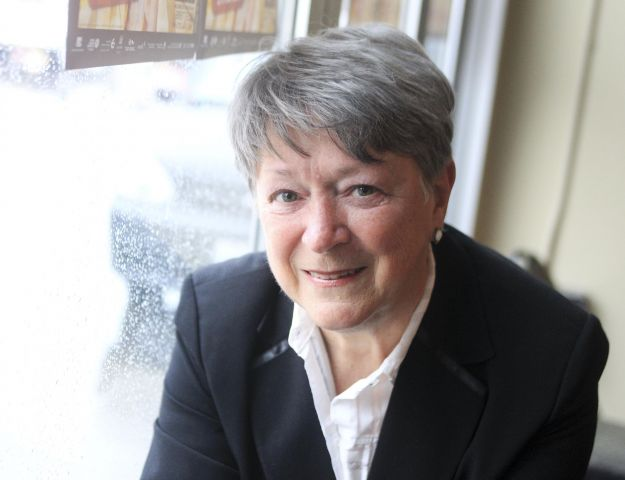Photographie en couleur d'une femme d'âge mûr, portant un chemisier blanc et une veste noir. Elle sourit à la caméra. L'arrière-plan est flou.