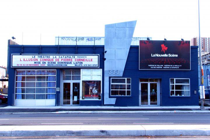 Photographie en couleur d'un théâtre en brique à un étage, peint en bleu foncé, avec plusieurs portes et fenêtres en verre. Une enseigne annonce que la prochaine pièce sera L'Illusion comiquede Corneille, présentée par le Théâtre la Catapulte.