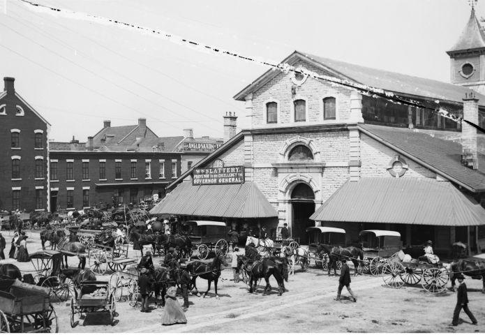 Photographie en noir et blanc d'un bâtiment à trois étages en pierre, avec des auvents. De nombreuses personnes ainsi que différents types de bogheis tirés par des chevaux attendent sur la place devant le bâtiment.