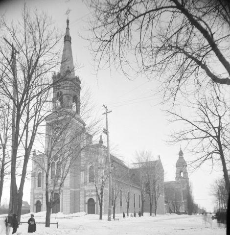 Photographie en noir et blanc d'une église vue en hiver. Une maison, des arbres et quatre personnes font partie du paysage. Une partie de la photographie est masquée, à cause de l'objectif photographique.