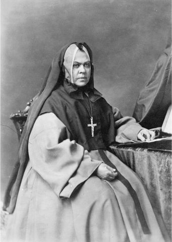 Photographie en noir et blanc d'une religieuse d'âge mûr, assise sur une chaise avec, une table à sa gauche. Elle porte un voile noir ainsi qu'une croix. Elle affiche un air sérieux.