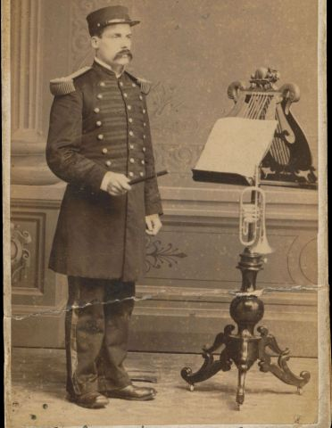 Sepia photograph of a middle-aged man wearing a uniform and a large mustache. He stands in front of a richly carved lectern which holds music scores and a trumpet. The name and title of the subject are handwritten at the bottom of the picture.