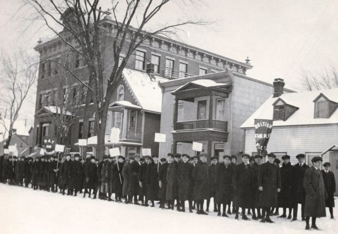 """Black and white photograph of a column of fifty young men dressed for the winter. They carry signs and banners with messages such as """"Pay our Teachers"""" and """"British Fair Play Please."""" In the background, a three-storey brick building and three houses."""