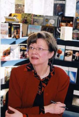 Colour photograph of a mature woman, three-quarter view. She has short brown hair, and she wears glasses, a red and black printed blouse, a red jacket, and a pearl necklace. She sits, arms crossed on a table, a pen in her right hand. In the background, a book display.