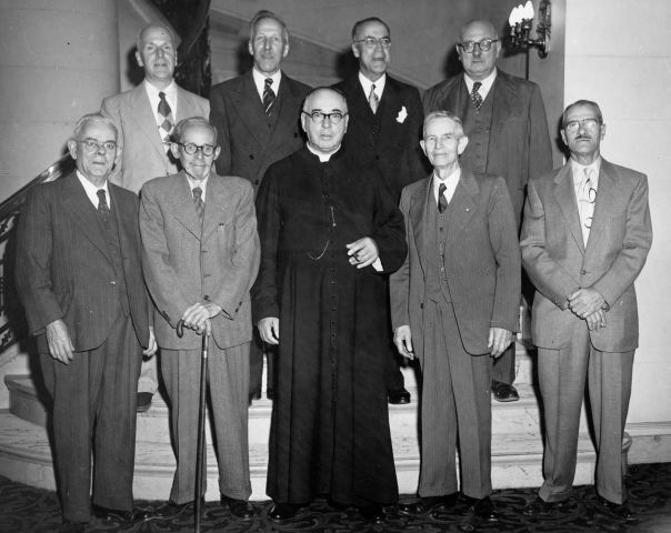 Black and white photograph of nine elderly men. Five men stand at the bottom of a staircase, and four stand behind them on the second step. Eight of the men are dressed in suits and ties. The man in the centre is dressed in a black cassock and holds a cigar. One of the men in the front row leans on a cane.