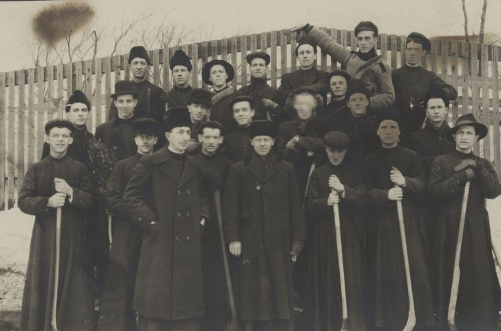 Black and white photograph, taken in winter, of a group of about fifteen young men, accompanied by some adults. They are arranged in three rows, in front of a wooden fence. The youngest wear the cassock and hold hockey sticks. Adults wear long winter coats and fur hats. One of them stands in front of the group, the other in the center of the photo, the other two on the sides.
