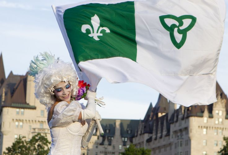 Colour photograph of a young woman, in three-quarter view, holding a wreath of flowers and a large Franco-Ontarian flag. She is dressed all in white and wears carnival attire. In the background, the Chateau Laurier, Ottawa's iconic hotel.