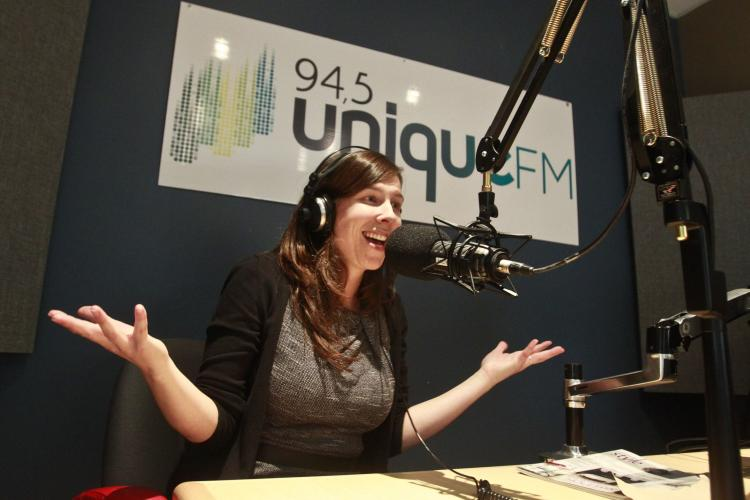 """Colour photograph of a middle-aged, smiling woman in a radio studio. She wears headphones and speaks into a suspended microphone. She sits at a table with her arms raised, hands open, palms up. Behind her, a sign with the words """"94,5 Unique FM."""""""