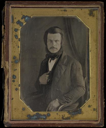 Black and white studio photograph of a man with a mustache and piercing eyes, dressed in a three-piece suit. He sits on a chair. The gold frame surrounding the photograph is heavily damaged.