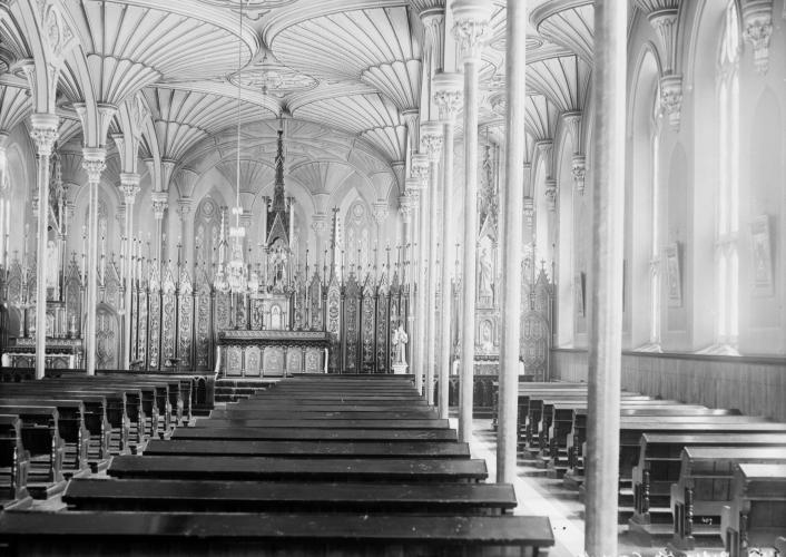 Black and white photograph of the interior of a small church, with many benches in rows. The vaulted ceiling, made of carved wood, is supported by thin columns. The altar is very ornate. orné.