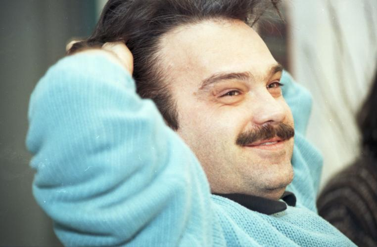 Colour photograph of a middle-aged man, three-quarter-view. He is smiling, sitting with both hands behind his head. He has brown hair and a mustache. He wears a pale blue sweater.