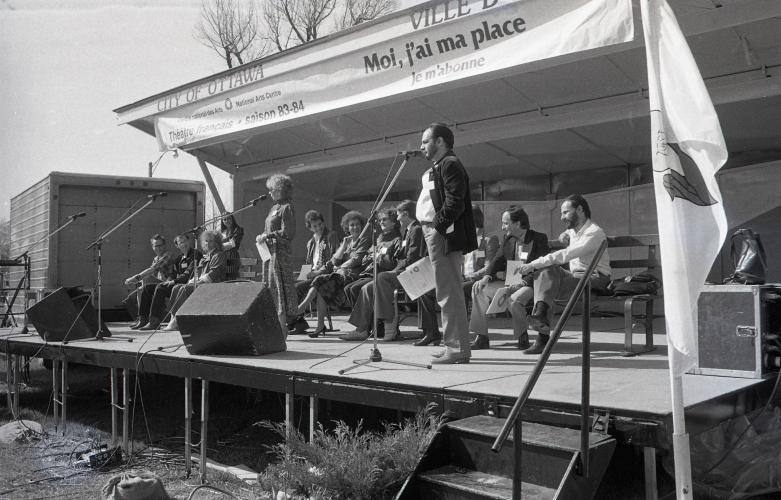 """Black and white photograph of a middle-aged man and woman standing at microphones on an outdoor stage. Behind them, around ten people sitting on benches. Written on a banner above the stage: """"Centre national des Arts–National Arts Centre; Théâtre français saison 83-84; Moi, j'ai ma place; Je m'abonne."""""""
