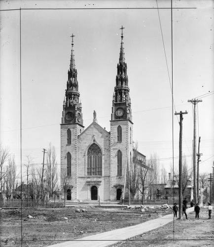 Black and white photograph of a large three-storey white stone church with a large stained glass window in the Centre front. The space in front of the church is vacant. Some small houses, as well as trees and electrical wires appear on either side of the church.