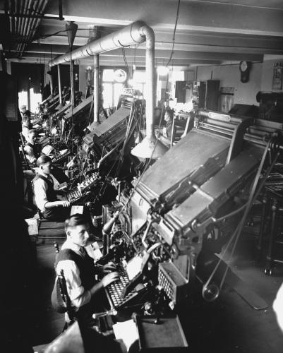 Black and white photograph of five men in shirts, vests and ties in an industrial workshop. They sit in front of imposing printing machines with keyboards.